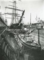 Historische Bilder aus dem Hamburger Hafen - ein Segelschiff und eine Barkasse / Schlepper liegen im Trockendock der Reiherstiegwerft.