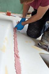 Aufbringen von Spachtelmasse / Epoxitspachtel am Deck des Segelboots.