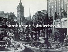 Bei der Wandrahmsbrücke haben Kähne festgemacht, die Gemüse für den Markt am Deichtorplatz geladen haben. Bäuerinnen tragen mit Körben die Ernte an Land, um ihre Ware auf den Deichtormarkt zu bringen. Hoch ragt der Uhrenturm der Wandrahmsbrücke a