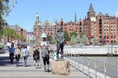 Störtebeker Denkmal am Magdeburger Hafen in der Hamburger Hafencity - im Hintergrund Backsteinarchitektur. Spaziergänger in der Sonne am StörtebekerUfer.