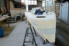 Feinarbeiten am Deck des Daysailers - mit einem starken Lichtstrahler werden kleine Unebenheiten sichtbar gemacht und ausgebessert.