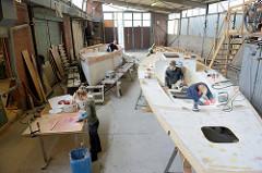Feinarbeiten am Deck des Daysailers - mit einem starken Lichtstrahler werden kleine Unebenheiten sichtbar gemacht und ausgebessert - Spachtelmasse für die Innenseite des Schiffsrumpf wird angerührt.