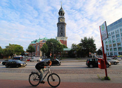 Blick über die Ludwig Erhard Strasse zum Kirchturm des Michels; Bushaltestelle Michaeliskirche, Radfahrer und Autoverkehr.