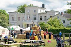 Bauernmarkt, Hoffest auf dem Gut Wulksfelde; Kinder spielen auf Strohballen, im Hintergrund das alte Gutshaus.