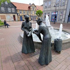 Bronzeskulpturen am Marktbrunnen vor dem Alten Rathaus in Lüchow - zwei weibliche Bronzeskulpturen / Leinenweberinnen; eine Altbäuerin prüft das Leinen ihrer Tochter. Mitte des 19. Jahrhunderts wurden in Lüchow ca. 1 Mio. Meter Leinen gewebt und wurd