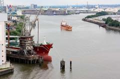 Blick auf die Rethe in Hamburg Wilhelmsburg - ein Frachtschiff fährt Richtung Köhlbrand / Süderelbe; im Vordergrund wird die Ladung eines Massengutfrachters gelöscht.
