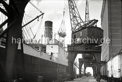 Einer der Portalkräne hat eine Ladung gefrorener Tierhälften in seinem Transportnetz - am Hafenkai liegt ein Kühlfrachter. Recht das UNION KÜHLHAUS in Hamburg Neumühlen. (ca. 1939)