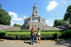 Hamburger Bismarck-Denkmal - Statue aus Granit auf der Elbhöhe im Alten Elbpark - fertiggestellt 1906; Architekten Johann Emil Schaudt und vom Berliner Bildhauer Hugo Lederer. Touristen stehen vor der Denkmal-Anlage und machen Fotos.