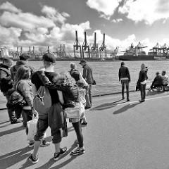 Anleger der Hafenfähre in Oevelgönne - Fahrgaste warten auf das Schiff; im Hintergrund die Hafenkräne vom Container Terminal Burchardkai im Hamburger Hafen.