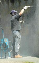 Der Sockel vom Hamburger Bismarckdenkmal ist mit Grafitti beschmiert; ein Arbeiter säubert den Stein mit Druckluft.