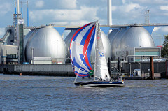 Segelboot mit Spinnaker im Wind auf der Elbe - im Hintergrund das Klärwerk der Hamburger Wasserwerke auf Köhlbrandhöft / Steinwerder; Faultürme.