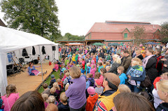 Kindertheater auf dem bauernmarkt vom Biohof Wulksfelde - die Kinder stehen dichtgedrängt vor dem Zelt.