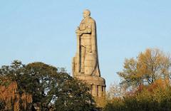 Hamburger Bismarck-Denkmal - Statue aus Granit auf der Elbhöhe im Alten Elbpark - fertiggestellt 1906; Architekten Johann Emil Schaudt und vom Berliner Bildhauer Hugo Lederer. Bäume mit herbstlichen Blättern am Elbpark.