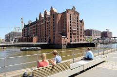 Mittagspause in der Sonne am Störtebekerufer in der Hamburger Hafencity - eine Barkasse fährt durch den Magedeburger Hafen am ehem. Kaispeicher B, jetzt Internationales Maritimes Museum - dahinter Gebäude an der Elbtorpromenade.