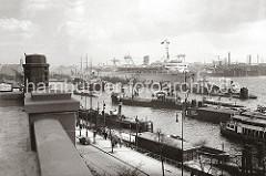 Blick von der Hochbahnstation Landungsbrücken auf den Niederhafen; Frachtschiffe und Schuten liegen am Kai oder an den Dalben in der Mitte des Hafenbeckens. An den Pontons haben Fähren und Fahrgastschiffe der Hafenrundfahrt fest gemacht. Neben dem