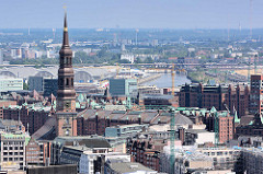 Kirchturm der St. Katharinenkirche, dahinter die historischen Lagergebäude der Hamburger Speicherstadt - in der Bildmitte der Oberhafenkanal und die Gemüsehallen in Hamburg Hammerbrook.