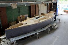 Das Deck vom Daysailor in eingesetzt - der fertig grundierte Schiffsrumpf wird mit einer Filzmatte vor Beschädigungen geschützt.
