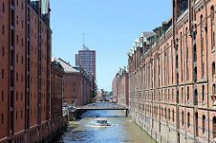 Fleet mit historischen hohen Speichergebäuden in der Speicherstadt Hamburg - unter den Kupferdächern sind Winden angebracht, die früher die Last von Schuten in die Lagerräume gehievt haben. Eine Barkasse fährt mit Touristen auf dem Brooksfleet - im H