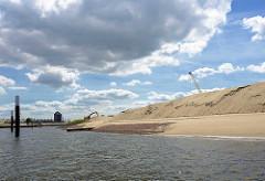 Eine künstliche Halbinsel wird als zukünftiger Park und Freizeitinsel im Hafenbecken vom Baakenhafen im Hamburger Stadtteil Hafencity aufgeschüttet - im Hintergrund das Hotelhochhaus an den Elbbrücken in Hamburg Rothenburgsort.