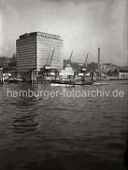 Das UNION KÜHLHAUS in Hamburg-Neumühlen; vor dem 1926 errichteten Gebäude stehen Kräne am Kai.  Eine Barkasse der Hafenpolizei fährt entlang der Duckdalben, die im Strom stehen.