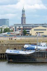 Bug von zwei Binnenschiffen am Auguste Viktoria Kai im Kaiser Wilhelm Hafen, eines der Hafenbecken im Hamburger Hafen - im Hintergrund die St. Michaeliskirche in der Hamburger Neustadt.