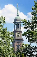 Kirchturm der St. Michaeliskirche zwischen Bäumen - Kupferkuppel mit Aussichtsplattform, Turmuhr - Wahrzeichen der Hansestadt Hamburg.