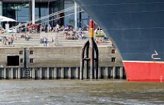 Bug des Kreuzfahrtschiffs QUEEN MARY im Hamburger Hafen, Terminal Hafencity; Schaulustige / Touristen sitzen auf den Treppen vor dem Unilevergebäude in der Sonne.