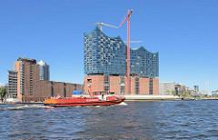 Das Löschboot OBERBAURAT SCHMIDT fährt auf der Norderelbe Höhe Elbphilharmonie elbaufwärts; im Hintergrund lks. Bürogebäude am Kehrwieder und re. die Einfahrt zum Grasbrookhafen.