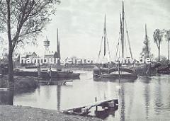 historisches Motiv vom Finkenwerder Fischereihafen - Fischerboote liegen vor Anker, ein Bootssteg führt ins Wasser. Im Hintergrund der Finkenwerder Wasserturm und Werftgebäude