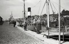 Fischdampfer liegen am Ausrüstungskai des Fischereihafens Hamburg Altona; dort Bunkern die Dampfer Kohle und nehmen Eis zur Kühlung des Fangs an Bord. Ein Fischer geht mit zwei Zink-Eimern zu seinem Schiff - eine einachsige Holzkarre / Schottsche Ka
