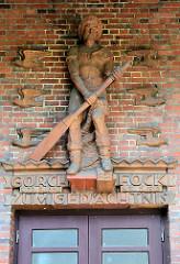 Gorch Fock Halle in Hamburg Finkenwerder, erbaut 1930 - Architekt Fritz Schumacher; ehemaliges Volkhaus und Bücherhalle. Skulptur Finkenwerder Fischer mit Ruder; Inschrift Gorch Fock zum Gedächnis.