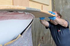 Das Schiffsdeck wird auf den Rumpf  aufgesetzt - überschüssige Epoxitmasse quillt aus der Fuge zwischen Deck und Bootsrumpf.