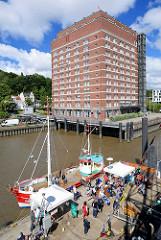 Fischkutter am Anleger in Hamburg Oevelgoenne; ehem. Kühlhaus in Hamburg Ottensen, jetzt Seniorenresidenz an der Elbe.