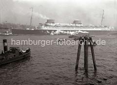Der Passagierdampfer EUROPA wird von den Schleppern in das Fahrwasser der Elbe gezogen, damit das Schiff seine Fahrt in seinen Heimathafen Bremen antreten kann. Von dort soll die Jungfernfahrt über den Atlantik nach New York starten. Barkassen und