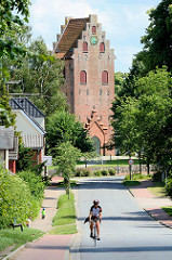 Blick durch den Neuen Weg in Sülfeld zum Kirchturm der Sülfelder Kirche, norddeutsche  sakralen Backsteinarchitektur mit Treppengiebel - Ursprungsbau aus dem 13. Jahrhundert.