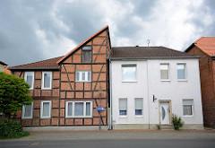 Historische und neue Architektur nebeneinander - Wohnhäuser in Lüchow; Fachwerkhaus mit halben Spitzdach / Giebel, kubisches Gebäude mit weisser Fassade.