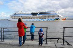 Das Kreuzfahrtschiff AIDAbella verlässt den Hamburger Hafen - Schaulustige beobachten die Ausfahrt des Passagierschiffs.