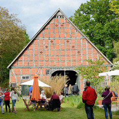Kulturelle Landpartie im Wendland / Hof in Luckau; Kaffeetrinken unter dem Sonnenschirm, Kunst auf der Tenne einer Fachwerkscheune.