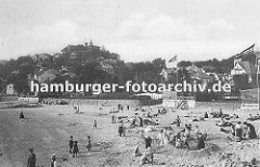 Blankeneser Strandszene um 1890; Kinder spielen im Sand, Mütter mit ihren Kindern sind dabei eine Sandburg zu bauen. Am Elbufer Strandlokale wie der Elb-Pavillon, Flaggen wehen im Wind. Im Hintergrund der Süllberg mit den Häusern des Elbdorfe