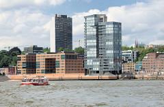 Blick über die Elbe - Wohnhäuser, Hochhäuser am Elbufer von Hamburg Altona / Grosse Elbstrasse. Barkasse mit Fahrgästen bei einer Hafenrundfahrt.