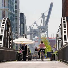 Blick durch den Kibbelsteg in der Hamburger Hafencity - Sonnenschirme, Fahrradfahrer; im Hintergrund Kräne am Hansahafen.