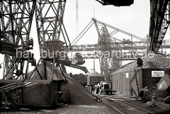 Auf dem Kai des Altonaer Kohlenlagers wird die angelandete Kohle gelagert. Die Greifer holen die Ladung von dem Frachtschiff und füllen die Kohle in einen Trichter, von dem über Förderbänder das Schüttgut verteilt wird.  (ca. 1938)