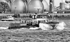Das Löschboot Oberbaurat Schmidt in Fahrt - Gischt spritz am Bug des Feuerwehrschiffs - im Hintergrund die Faultürme des Hamburger Wasserwerks auf Steinwerder / Köhlbrandhöft.