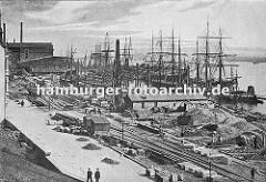 Bauarbeiten am Altonaer Hafenkai ca. 1905; Baumaterialien wie Bretter, Holzstämme und Sand liegen am Elbufer. Dazwischen verlaufen die Schienen der Hafenbahn, im hinteren Bereich stehen Güterwaggons. (ca. 1900)