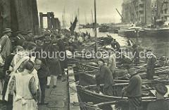 Fischerboote haben am Ponton des Altonaer Fischmarktes angelegt. Die Fischer an Bord preisen Ihre Ware an - die Besucher und Besucherinnen des Fischmarktes gehen an den Booten entlang und begutachten die Fische.  (ca. 1928)