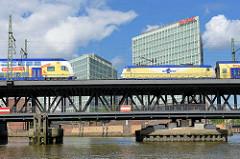 Oberhafenbrücke über den Oberhafenkanal; zwei Metronomzüge überqueren die Strassenbrücke / Eisenbahnbrücke; Stahlkonstrukiton auf zwei Etagen; im Hintergrund das Verwaltungsgebäude vom Spiegelverlag an der Ericusspitze im Hamburger Stadtteil Hafencit