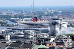 Blick über die Gebäude und Dächer der Hamburger Hafencity - hinter dem Marco Polo Tower liegt das Kreuzfahrtschiff QUEEN MARY am Terminal an der Norderelbe.