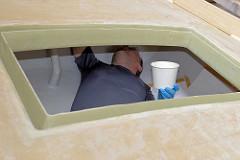 Verspachteln der Fugen zwischen Rumpf und Deck im Innenraum des Seglers.