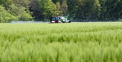 Kornfeld im Wendland - ein Bauer sprüht mit seinem Traktor....