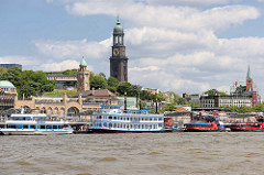 Fahrgastschiffe an den St. Pauli Landungsbrücken - hinter dem Uhrenturm / Pegelturm der Kirchturm des Michels, ganz rechts die schwedische Gustaf-Adolf-Kirche.